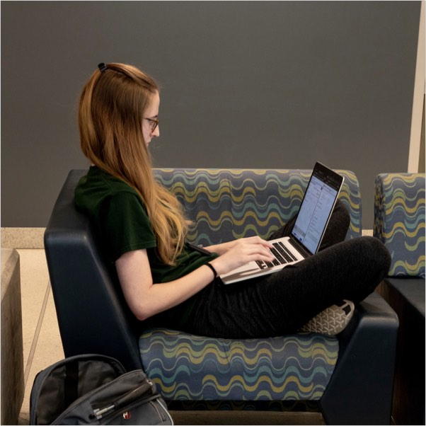 A student working remotely from a laptop while relaxing on a couch.